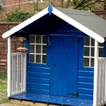 Playtime In The Garden With A Wooden Playhouse