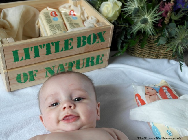 baby smiling with a crate in the picture and flowers