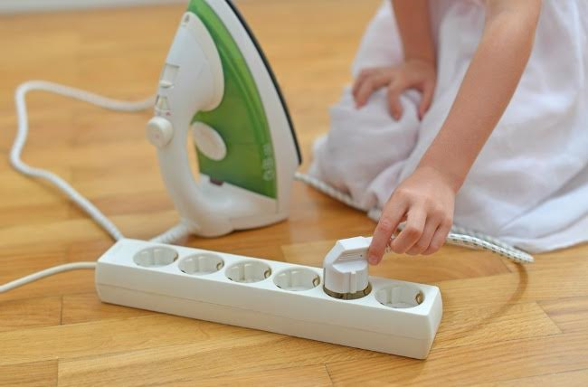 child plugging in an iron into an extension cable