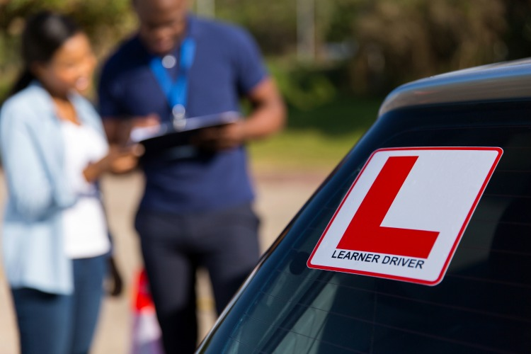 learner driver and instructor behind a car