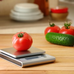 Fresh tomato with digital kitchen scales on wooden table