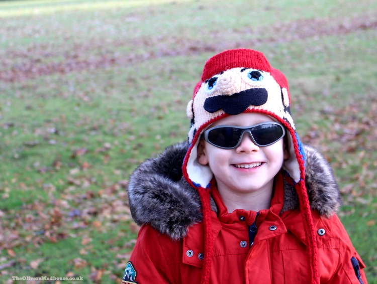 boy wearing a red coat and hat smiling and wearing sunglasses