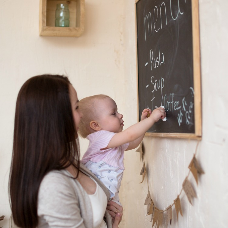 Mom and Toddler Daughter playing menu planning to write to the blackboard and chalk, lifestyle real interior, baby helps working mom,
