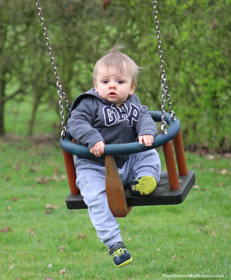 baby in a child swing on the park