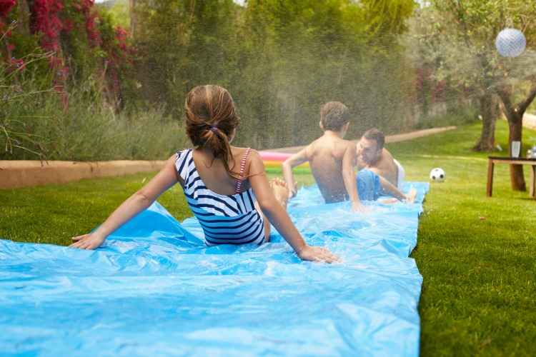 Rear View Of Family Having Fun On Water Slide In Garden