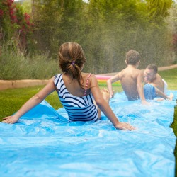 Rear View Of Family Having Fun On Water Slide In Garden