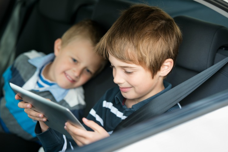 Children playing through ipad touchscreen inside the car