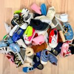 Close up on big pile of baby shoes. Untidy stack of boy and girl toddler