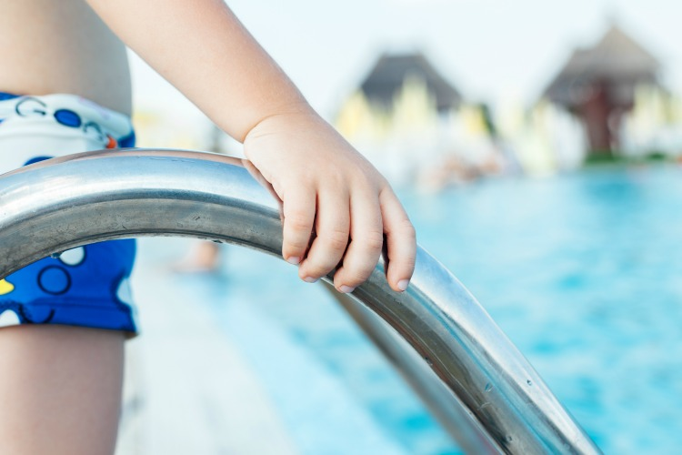 Closeup of child enters the swimming pool