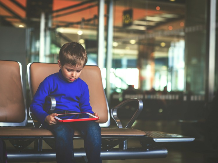 little boy looking at touch pad while travel in the airport, kids travel