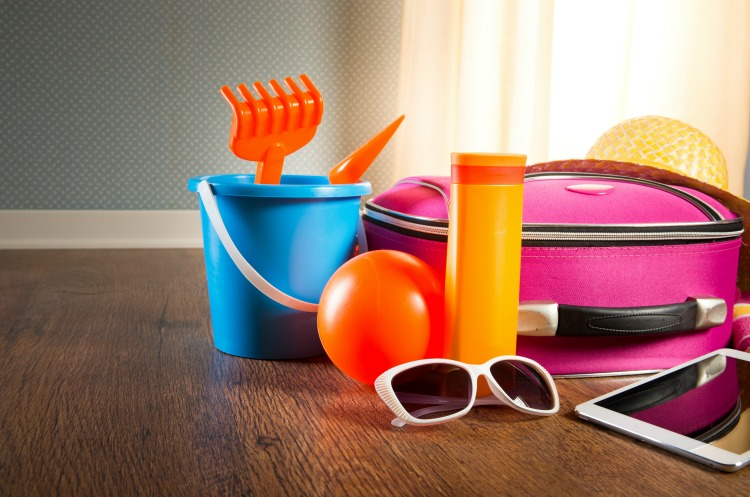 Summer vacations packing with colorful accessories and digital tablet.