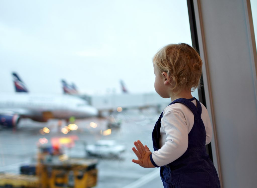 Kid near the window in the airport.