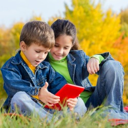 Two smiling kids playing with tablet pc and sitting on the autumn lawn
