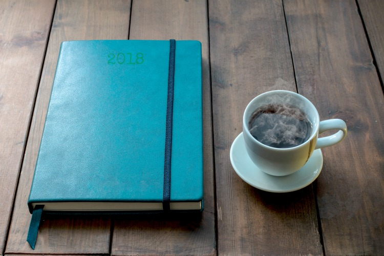Blue notebook with cup of coffee on wooden background. Metaphor of a creative process.