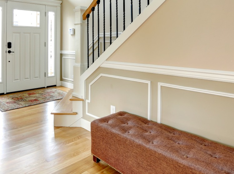 Luxury home interior. View of entrance door, stairs with iron and wood railings and ottoman.