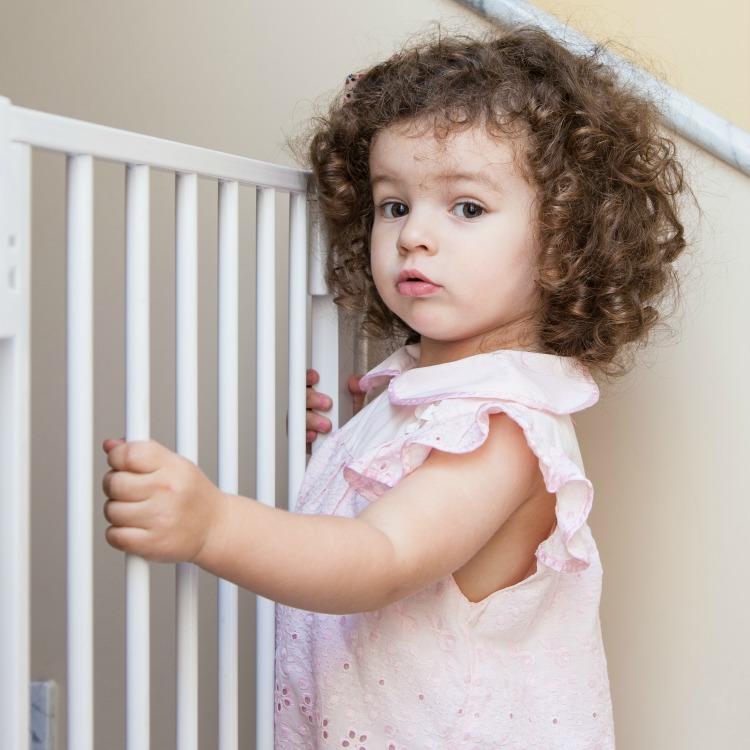 Portrait of a cute curly-hair girl near stair gate
