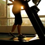 Young asian woman exercising on a treadmill